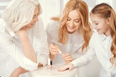 Loving ladies doing manicure in family circle. Happiness is a family gathering. Selective focus on a cheerful mature women standing next to her beautiful mom and Stock Photography
