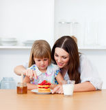 Loving little girl and her mother having breakfast Stock Images