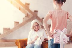 Loving little girl hiding gift box for grandmother. Ive got something for you. Selective focus on a thoughtful grandchild standing with a beautifully wrapped royalty free stock photo