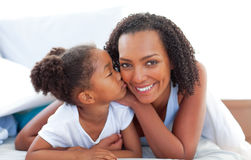 Loving little girl kissing her mother lying on bed Stock Photos