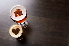 Loving local craft beer. House and heart silhouettes in two glasses of fresh beer on pub table, view from above royalty free stock photography
