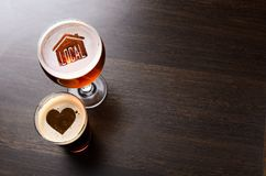 Loving local craft beer. House and heart silhouettes in two glasses of fresh beer on pub table, view from above stock image