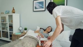 Loving man bringing breakfast in bed for sleeping girlfriend kissing smiling. Loving man is bringing breakfast in bed for sleeping girlfriend kissing and smiling stock video footage