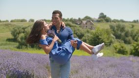 Loving man carrying charming woman in rural field