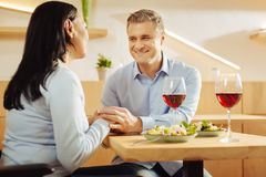 Loving man and a disabled woman holding hands. Red wine. Content disabled dark-haired women and a handsome smiling well-built men sitting in a cafe and holding Stock Images