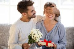 Loving man with flowers closing eyes of woman making surprise royalty free stock images