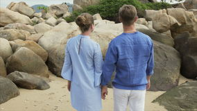 Loving man and girl talking, walking along the sea beach holding hands, back view stock video footage