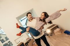 Loving man wearing white sweater caring his wife in hands. Wife in hands. Loving men wearing white sweater caring his wife in hands while standing in their own royalty free stock photography