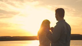 Loving man and woman dance in bright rays of sun on the background of the lake. Young couple dancing at sunset on beach stock video footage
