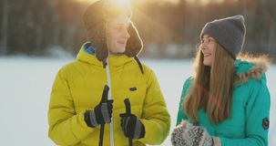 Loving man and woman skiing in the winter forest doing outdoor activities leading a healthy lifestyle. slow motion stock video