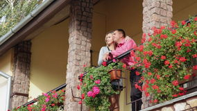 Loving man and woman standing on the balcony with red flowers stock video
