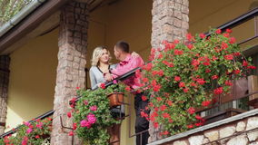 Loving man and woman standing on the balcony with red flowers stock video footage