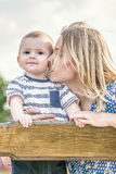 Loving mather kissing a baby boy on a wooden bench outdoor on nature at sunny summer say. Emotions of love Royalty Free Stock Images