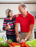 Loving mature couple cutting  in  kitchen Stock Photos