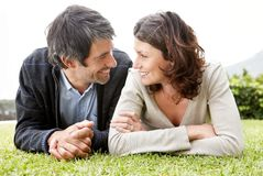 Loving mature couple lying on lawn - Outdoor Royalty Free Stock Photos