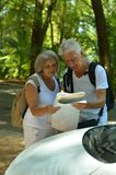 Mature couple with map near car Stock Images