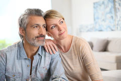 Loving mature couple sitting at home. Loving mature couple looking towards the future Stock Image