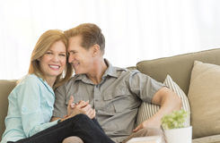 Loving Mature Couple Sitting On Sofa At Home Stock Photo