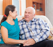 Loving mature couple on sofa at home Royalty Free Stock Image