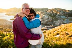 Loving mature couple traveling, standing on the top of rock, exploring. Active men and women hugging and kissing, Happily smiling. Scenic view of mountains and royalty free stock image