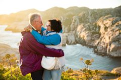 Loving mature couple traveling, standing on the top of rock, exploring. Active men and women hugging and kissing, Happily smiling. Scenic view of mountains and royalty free stock photo