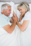 Loving mature man and woman lying in bed. Loving mature men and women lying in bed at the home Royalty Free Stock Images