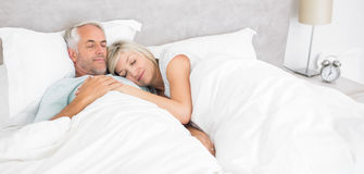 Loving mature man and woman lying in bed Royalty Free Stock Photos