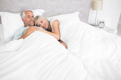 Loving mature man and woman lying in bed Stock Photos