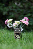 In Loving Memory. A grave marker 'In Loving Memory of a Dear Daughter' on a black and gold metal plate set on a vase holding pink and yellow carnations royalty free stock photo
