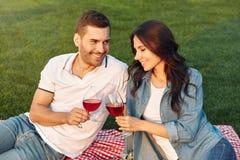 Man looking at his girlfriend and clicking wine glasses. Loving men looking at his girlfriend and clicking wine glasses together outdoors stock images