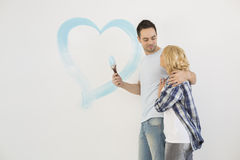 Loving mid-adult couple with painted heart on wall Stock Photography