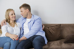 Loving mid adult couple sitting on sofa at home Stock Photos