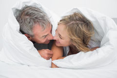 Loving middle aged couple under the duvet stock image