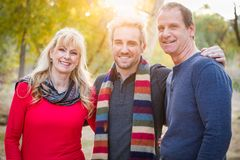 Loving Middle Aged Parents and Adult Son Portrait Outdoors. Loving Middle Aged Parents with Their Young Adult Son Portrait Outdoors stock images