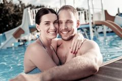 Loving millennial couple embracing in swimming pool royalty free stock image