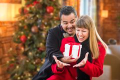 Loving Mixed Race Couple Sharing Christmas In Front of Decorated Tree. Mixed Race Couple Sharing Christmas In Front of Decorated Tree stock photo
