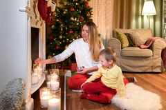 Loving mom is lighting some candles on a fireplace. Her little son is watching her. Young mother and son by a fireplace on Christmas royalty free stock images