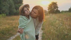 Loving moms puts on daughter knitted blanket, hugging child. Summer nature background, golden hour stock footage