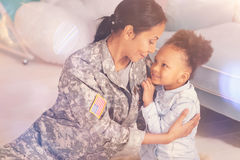 Loving mother in camouflage embracing her petite daughter Royalty Free Stock Photo