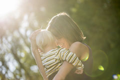 Loving Mother Carrying her Child at the Park Royalty Free Stock Photos