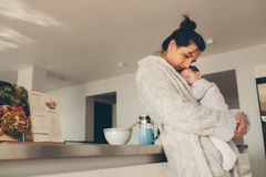 Loving mother carrying her newborn boy in kitchen Stock Photo