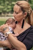 Loving mother cradling her baby boy on her shoulder outside. Loving young mother cradling her adorable baby boy on her shoulder while standing outside in a park stock photos