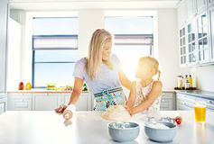 Loving mother and daughter baking in the kitchen. Kneading a pile of dough while chatting to each other with bright sun flare on their faces Stock Images