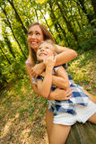 Loving Mother And Daughter. Beautiful young mother and her daughter sitting on fallen tree in the forest and enjoying Royalty Free Stock Photo