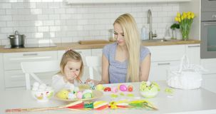 Loving mother and daughter coloring eggs stock footage