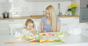 Loving mother and daughter coloring eggs Royalty Free Stock Photos