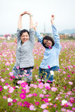 Loving mother and daughter do the arms stretched at flowers meadow. Stock Image