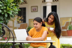 Loving mother and daughter with laptop outdoors. Mother and daughter working on laptop outdoors Royalty Free Stock Photography