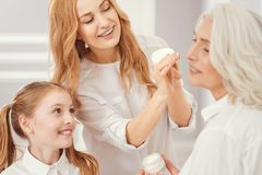 Loving mother and daughter taking care of granny. She is so beautiful. Selective focus on thoughtful grandchild and mother smiling while applying an anti aging Stock Image