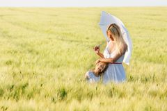 Loving mother and daughter under white umbrella Royalty Free Stock Photography